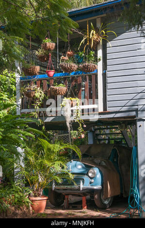 Veteran Morris car and hanging baskets clutter the facade of a Queenslander-style timber home ca. 1913, Brisbane, Australia - Stock Image