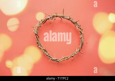 Crown of thorns like Jesus Christ wore with drops of blood on tips of thorns with bokeh lights over coral background. Perfect for Easter. - Stock Image