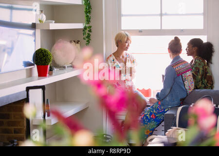 Young women friends drinking coffee and talking in apartment window - Stock Image