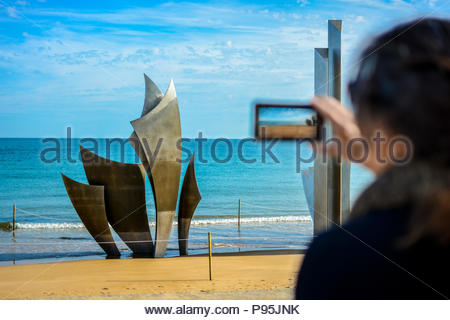A woman photographs Les Braves Memorial on Omaha Beach in the village of  St. Laurent-sur-Mer in Normandy, France commemorating the D Day invasion - Stock Image