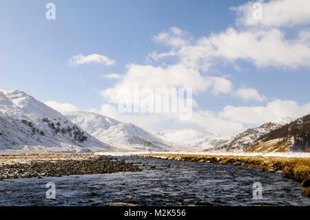 The River Findhorn winding through the Findhorn valley below the snow-covered Monadhliath Mountains in Inverness - Stock Image