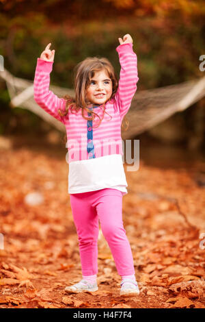 Happy little girl in autumn park, enjoying beautiful fall nature, raised up hands and playing with dry tree leaves - Stock Image