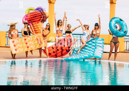 Summer holiday vacation at the pool - travel and enjoy the friendship for young beautiful people - group of women in bikini have fun with coloured tre - Stock Image