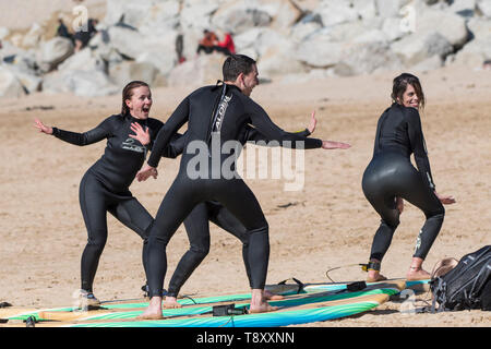 Surfers having fun posing for a photograph on Fistral Beach in Newquay in Cornwall. - Stock Image