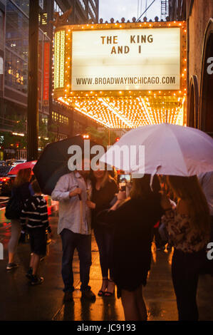 Chicago, United States. 14th Jun,  2017. The storm is not stopping these people from having fun as they stop for - Stock Image