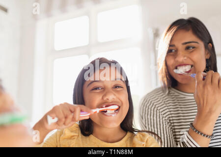 Portrait happy mother and daughter brushing teeth in bathroom - Stock Image