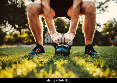 Cropped shot of fit young man doing kettlebell workout in the park, focus on hands holding kettle bell on grass. - Stock Image
