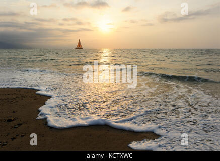 Sunset sailboat is a sailboat sailing along the ocean at sunset with the moon rising in the sky as a wave rolls - Stock Image