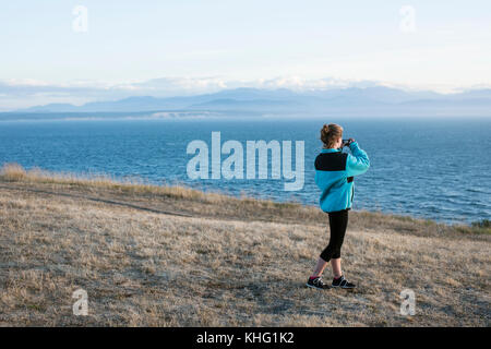 Teen girl taking picture of view with mobile phone - Stock Image