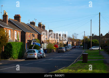 Suburban scene with road and cars parked and grass verges in Lingfield, Surrey, UK - Stock Image