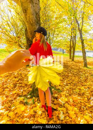 Autumn colors teen girl in woods in background behind hand holding big leaf - Stock Image