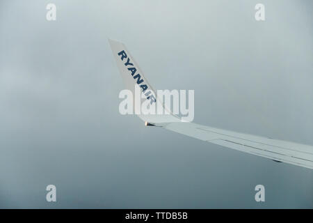view showing the wing tip of a ryanair passenger Boeing 737 jet whilst landing in fog - Stock Image