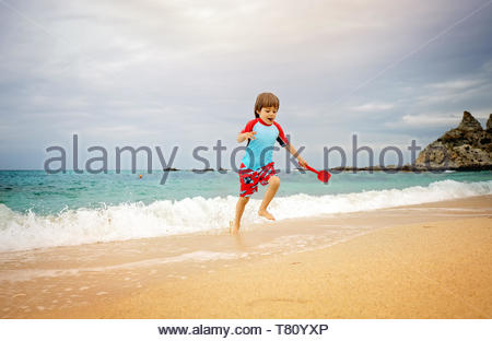 Kid wearing swimming trunks and sun protection t-shot playing on the beach - Stock Image