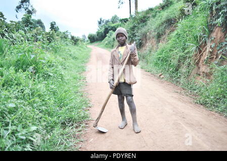 Young Ugandan boy stands in the middle of a dirt road holding farm tools, barefoot, looking at the camera - Stock Image