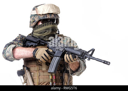 Studio shot of U.S. Marine equipped with rifle, helmet, and tactical gloves. - Stock Image