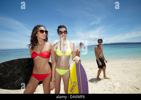 A group of friends posing with surfboards. - Stock Image
