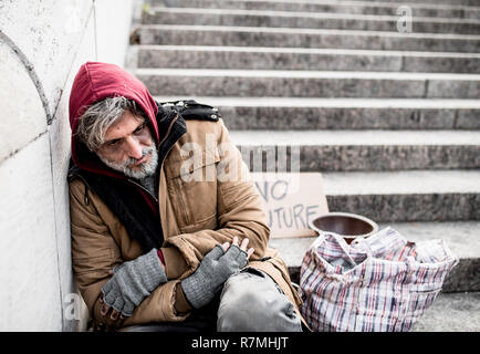 A homeless beggar man sitting outdoors in city asking for money donation. - Stock Image