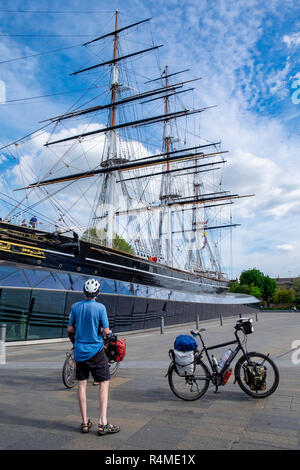Cycle tourists looking at the Cutty Sark ship, Greenwich, London - Stock Image