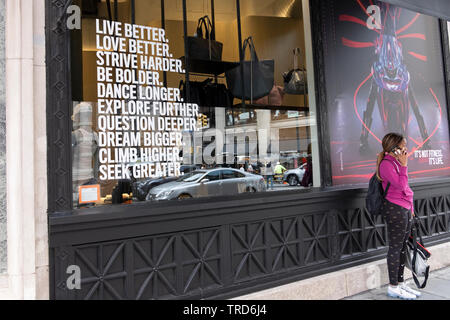 A woman on the phone outside an Equinox gym in Manhattan that has a most inspirational message in its window. - Stock Image