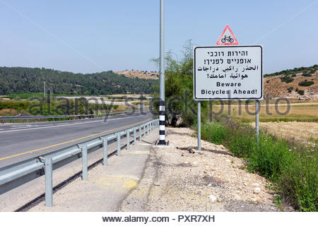'Beware Bicycles Ahead' road sign written in Hebrew, Arabic, and English on an Israel highway - Stock Image