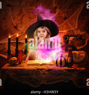 A little girl is dressed up in a halloween wicth costume with a glowing spell book of magic for an imagination or - Stock Image