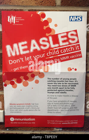 A poster with advice for patients about measles is seen in an NHS local doctors surgery waiting room in Warwickshire, UK, On May 14, 2019. - Stock Image