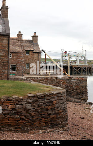 The old and the new in Stromness, Orkney. Old stone built houses on the waterfront and a catamaran gantry barge in the harbour. - Stock Image