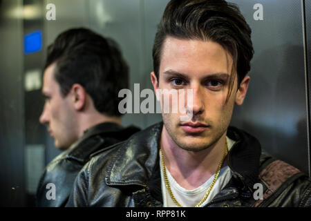 Handsome young man leaning against mirror in elevator or lift - Stock Image