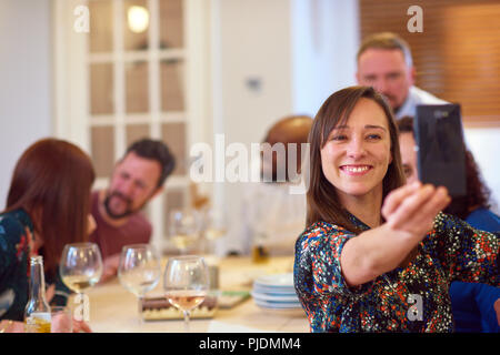 Friends taking selfie at dinner party - Stock Image