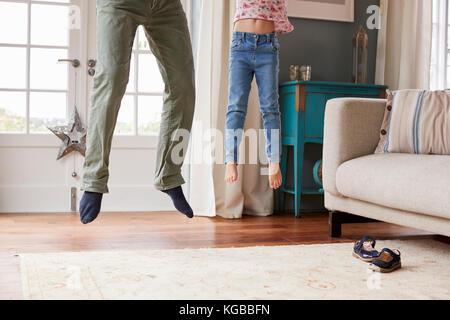 Girl and dad jumping in the air at home, low section - Stock Image