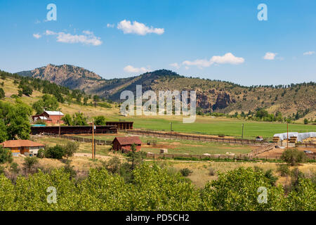 LOVELAND, CO, USA-18 JULY 18: A ranch, empty of horses,  outside of Loveland, with a row of low mountains behind. - Stock Image