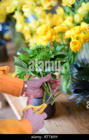 Making flower bouquets at floral arrangement party learning how to assemble flowers cutting stems - Stock Image