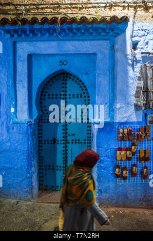 Chefchaouen, Morocco : A woman walks past a traditional wooden door in the blue-washed medina old town at night. - Stock Image