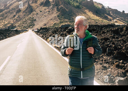 Adult aged senior man walking with backpack in long road at the mountain enjoying the alternative vacation trip and living a lifestyle adventure - ret - Stock Image