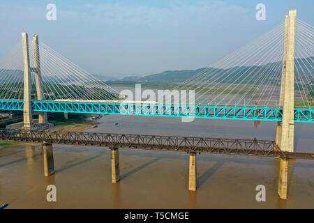(190423) -- CHONGQING, April 23, 2019 (Xinhua) -- Aerial photo taken on April 23, 2019 shows a bullet train running on the new Baishatuo Yangtze River railway bridge (Back) in Jiangjin of southwest China's Chongqing Municipality. The previous Baishatuo Yangtze River railway bridge, completed in 1959, will stop service after April 24. All trains will run on the new double decker steel truss cable stay railway bridge after that day. The new bridge has 4 tracks on the upper deck for passenger trains with a designed speed of 200 kilometers per hour and 2 tracks on the lower deck for cargo trains w - Stock Image