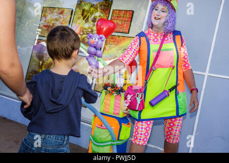 Miami Beach Florida Lincoln Road Mall pedestrian Antiques and Collectibles Market street performer woman clown costume balloon a - Stock Image
