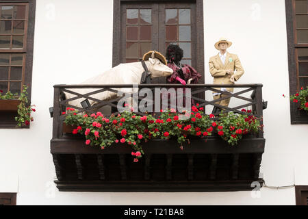 Display including a cow and male and female mannequins on a balcony above a restaurant in Santa Cruz de Tenerife. - Stock Image
