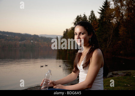 Portrait of a young woman in fitness attire holding a plastic disposable water bottle alongside lake. - Stock Image