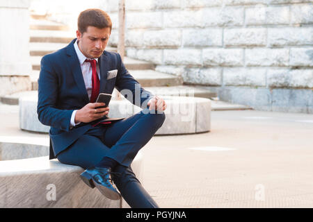 Young handsome businessman in a suit and tie consults the smartphone sitting on a marble bench in the park - Stock Image