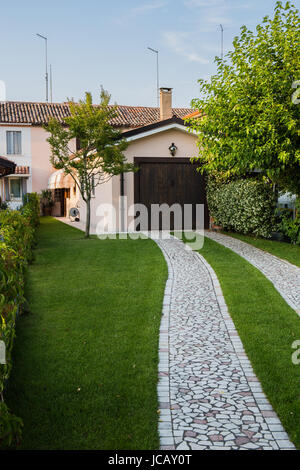 Garden with stone path leading to the garage - Stock Image