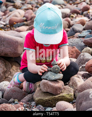 Dunbar, East Lothian, Scotland, UK. 21st Apr 2019. European stone stacking championship: Alex balances stones in the Quantity competition for children under 15 years of age –- most stones balanced vertically - at Eye Cave beach on the second day which comprises 2 competitions, a 3 hour artistic challenge and a children's competition.. The overall winner receives a trip to llano Earth Art Festival & World Stone Balancing competition in Texas in 2020. Credit: Sally Anderson/Alamy Live News - Stock Image