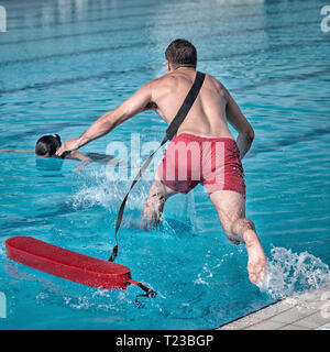 Lifeguard rushes into the pool. - Stock Image