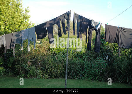 All grey and black clothes hanging on a washing line. - Stock Image