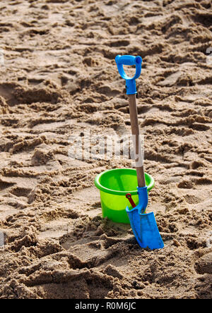 Child's bucket and spade on a sandy beach in Norfolk, UK. - Stock Image