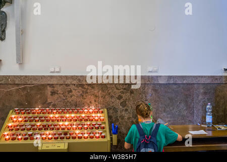 Inside the chapel where the icon of the Black Madonna of Czestochowa is shown, people ignite a candle to symbolize their prayer and write their intent - Stock Image