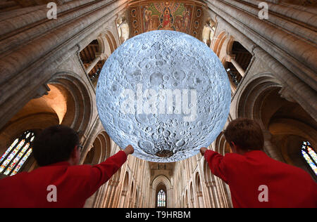 Choristers view Luke Jerram's 'Museum of the Moon' installation at Ely Cathedral in Cambridgeshire. The 7 metre diameter replica of the moon is the star attraction at the cathedral's science festival, 'The Sky's The Limit', which celebrates the 50th anniversary of the first moon landing. - Stock Image