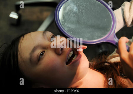 An orthodontist is a dentist who specializes in straightening crooked teeth. Female patient checking her braces - Stock Image