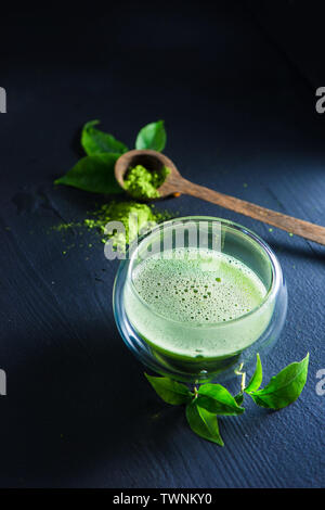 Matcha tea with foam in a double wall glass with a wooden spoon with matcha powder on a dark background with copy space - Stock Image