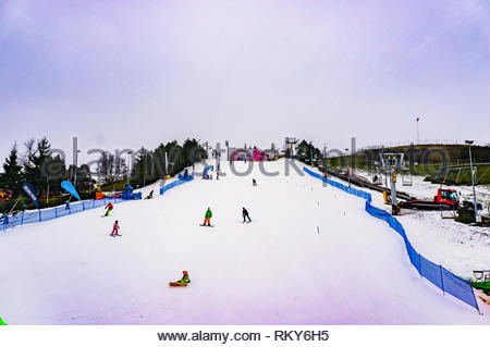 Poznan, Poland - February 10, 2019: Children learning to ski on a snow track at the Malta park on a cold winter day. - Stock Image