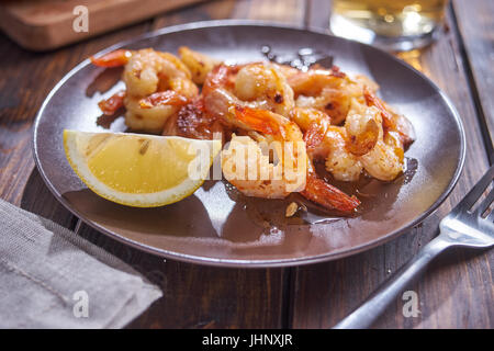 Fried shripms and glas on plate - Stock Image